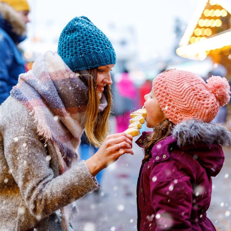 De jonge moeder en de dochter die witte chocolade eten behandelden vruchten op vleespen op traditionele Duitse Kerstmismarkt gelu stock fotografie