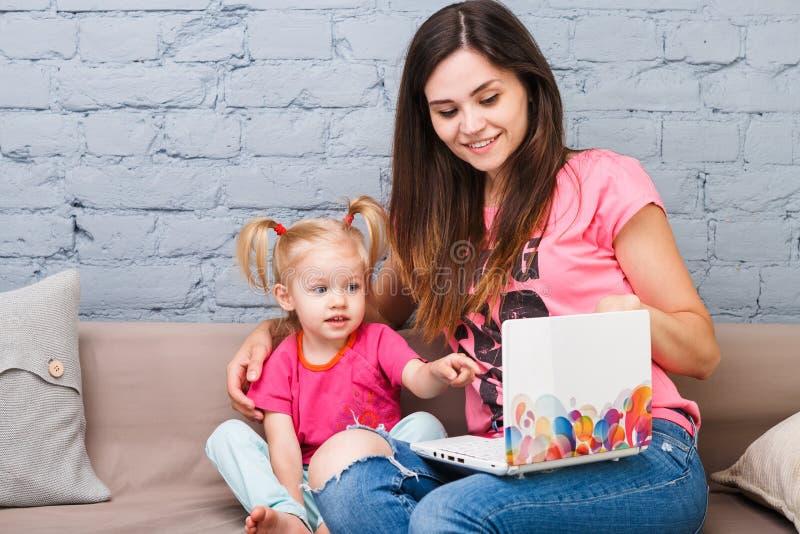 De jonge moeder en de dochter van twee jaar oud blonde gebruiken laptop computerlaptop wit binnen met heldere drukzitting op laag stock foto's