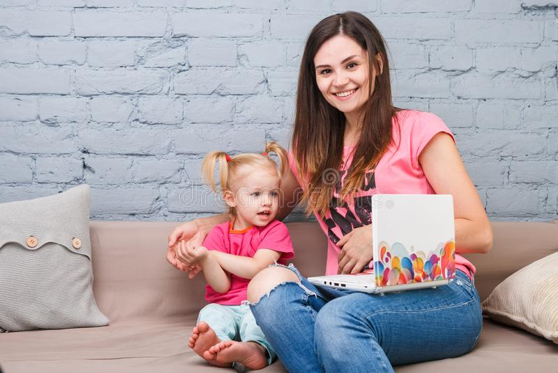 De jonge moeder en de dochter van twee jaar oud blonde gebruiken laptop computerlaptop wit binnen met heldere drukzitting op laag stock afbeeldingen