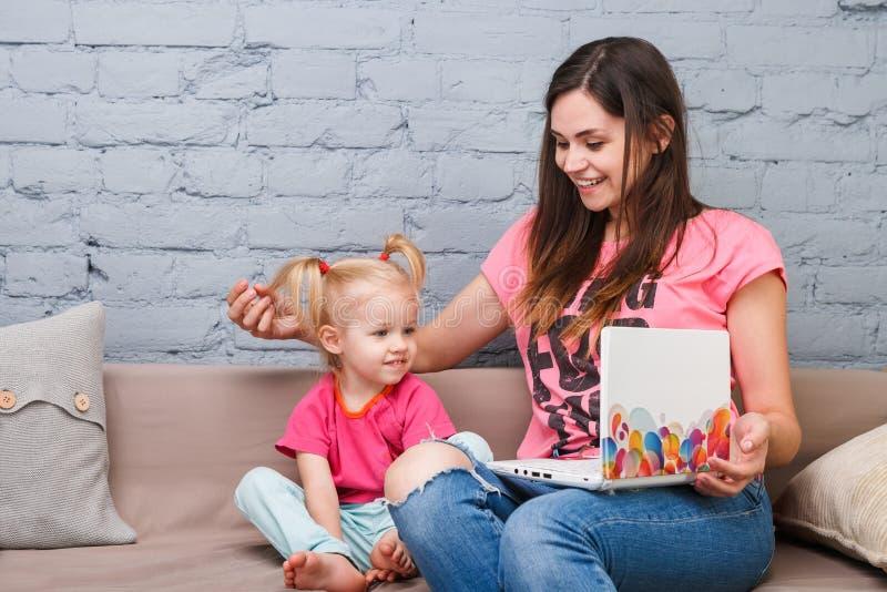 De jonge moeder en de dochter van twee jaar oud blonde gebruiken laptop computerlaptop wit binnen met heldere drukzitting op laag stock fotografie