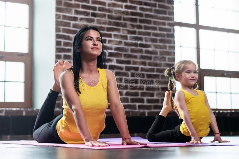De jonge moeder en haar dochter die dezelfde sportkleding dragen die koningscobra doen stellen tijdens groepsyoga opleiding royalty-vrije stock afbeeldingen