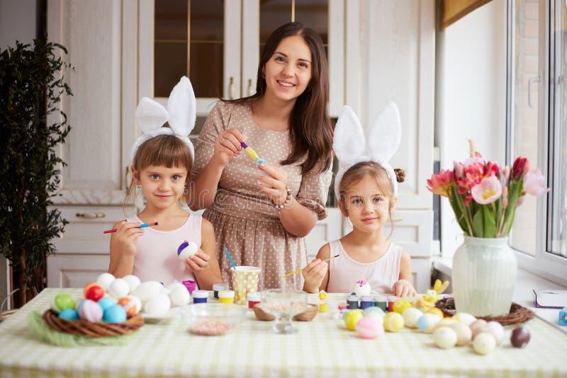 De jonge moeder en haar twee kleine dochters met de oren van het witte konijn op hun hoofdenkleurstof de eieren voor de Pasen die royalty-vrije stock fotografie