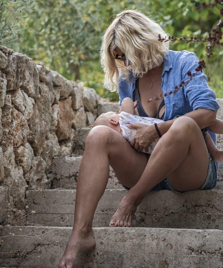 De jonge moeder geeft haar pasgeboren baby op de treden de borst stock afbeeldingen