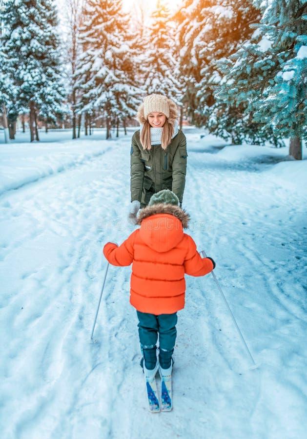 De jonge moeder is gelukkig en lach, die haar kind aanmoedigen een jongen van 4-6 jaar oude, eerste stappen van het ski?en op kin royalty-vrije stock afbeelding