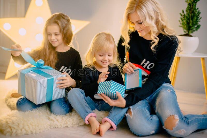 De jonge moeder giften aan geeft haar kleine dochters royalty-vrije stock afbeelding