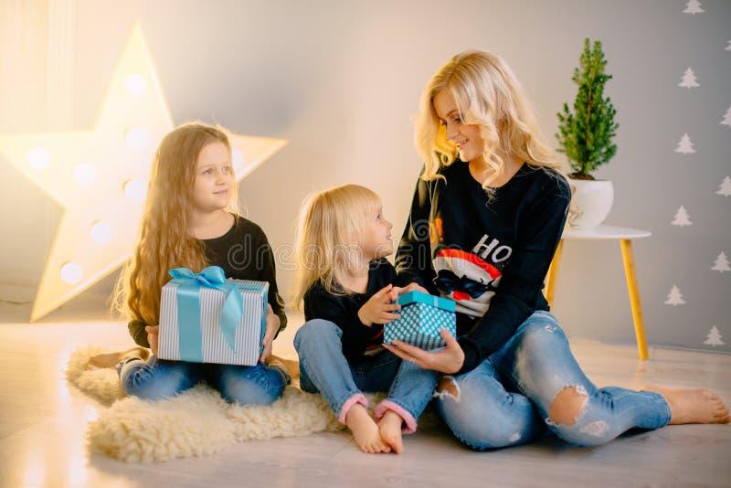 De jonge moeder giften aan geeft haar kleine dochters royalty-vrije stock fotografie