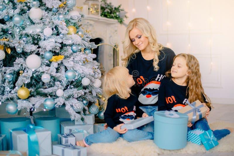 De jonge moeder giften aan geeft haar kleine dochters royalty-vrije stock afbeeldingen