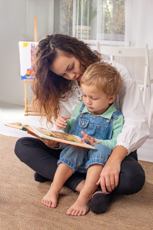 De jonge moeder of het kindermeisje met kleine kindjongen zit op de vloer op a stock afbeelding
