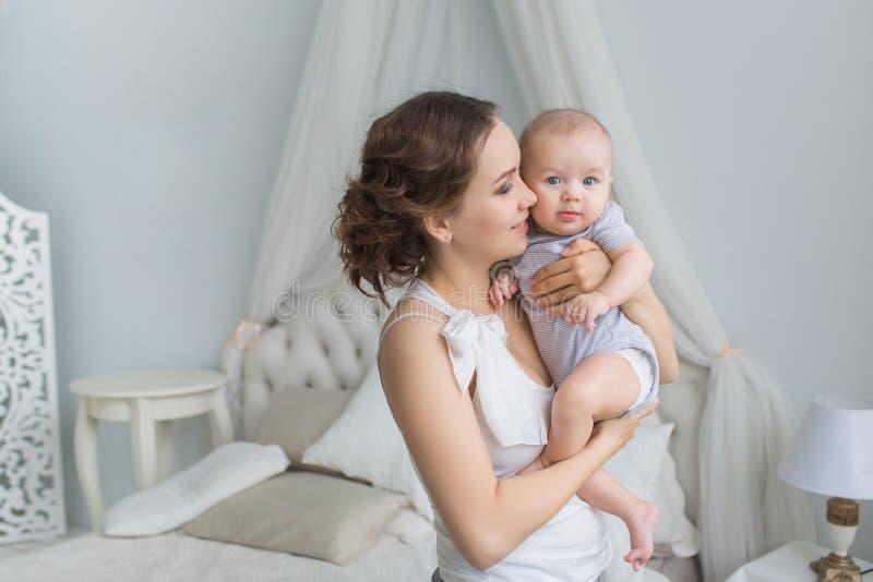 De jonge moeder houdt haar zuigeling op handen en bekijkt hem stock afbeeldingen