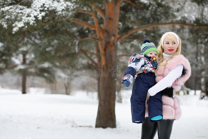 De jonge moeder loopt op een de winterdag met een baby in haar wapens in Th royalty-vrije stock foto's