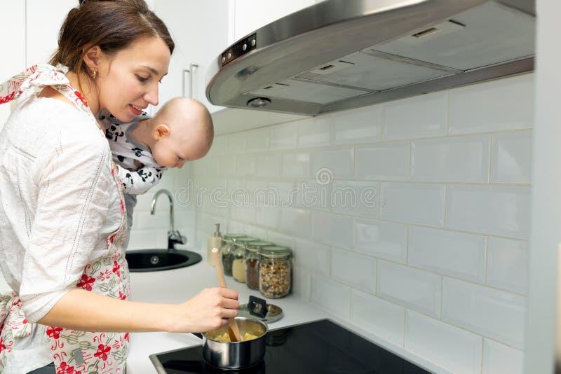 De jonge moeder met een baby op haar handen kookt het voedsel in een pot op het fornuis royalty-vrije stock fotografie