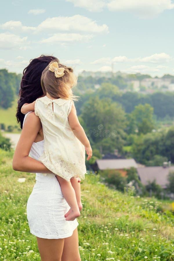 De jonge moeder met een kleine dochter in zijn handen die zich op de rand van de klip bevinden en onderzoekt de afstand over de s royalty-vrije stock foto
