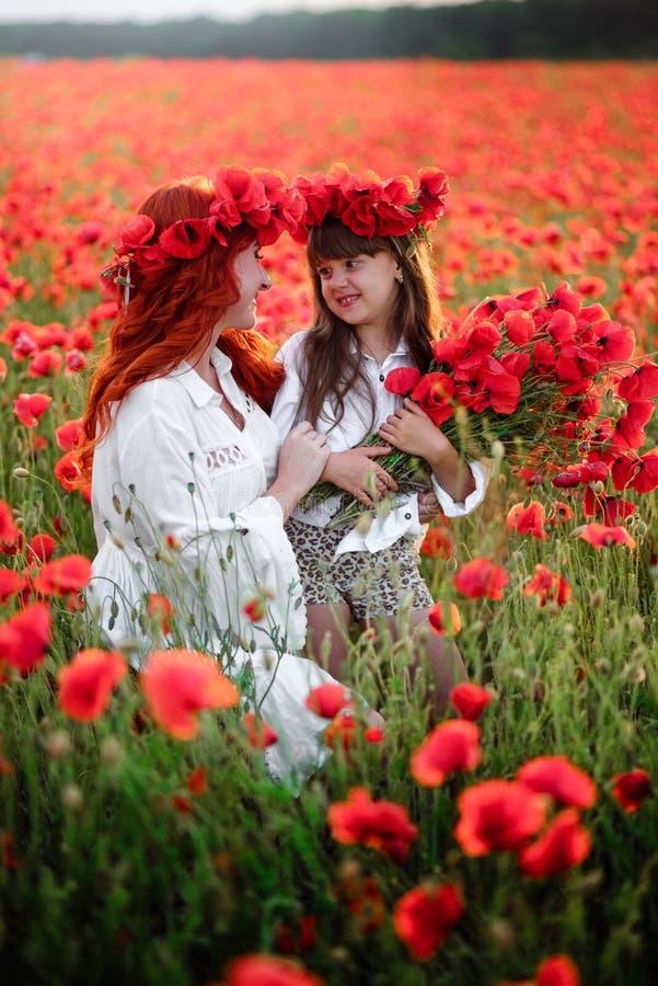 De jonge moeder met weinig dochter verzamelt rode papaverbloemen op een tot bloei komend gebied, omhoog sluit stock afbeelding