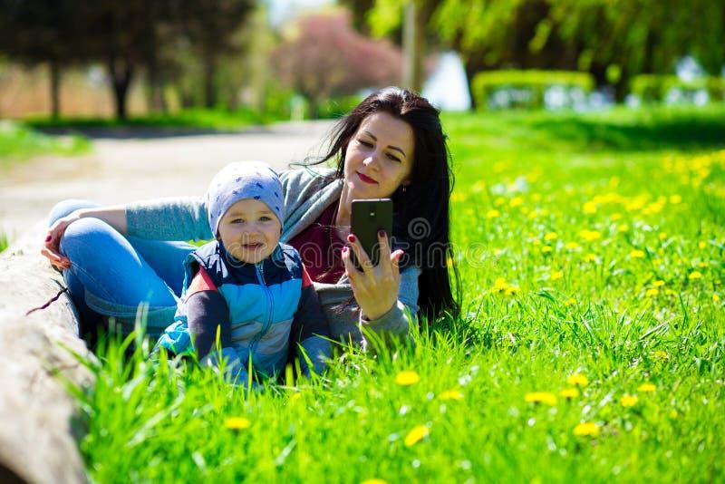 De jonge moeder met weinig kind ligt in open plek van paardebloemen stock foto's