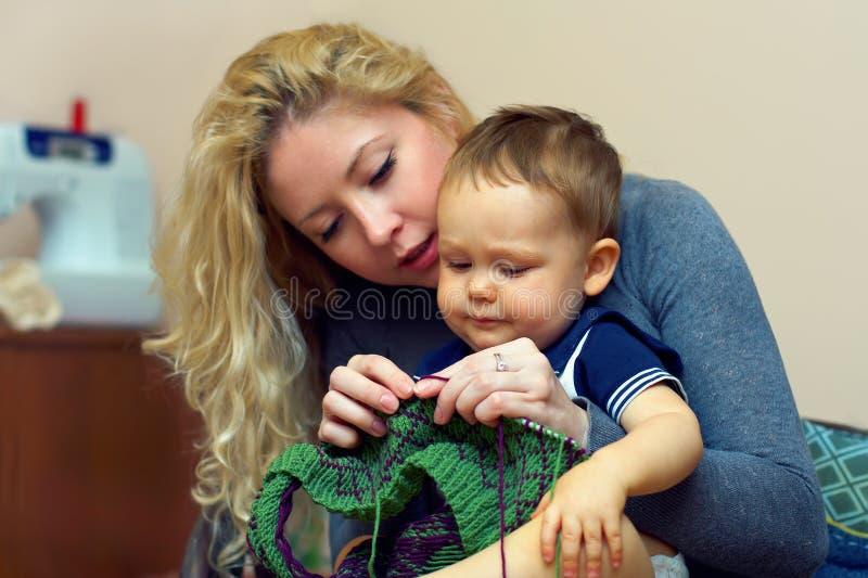 De jonge moeder onderwijst haar weinig babyjongen het breien royalty-vrije stock afbeeldingen