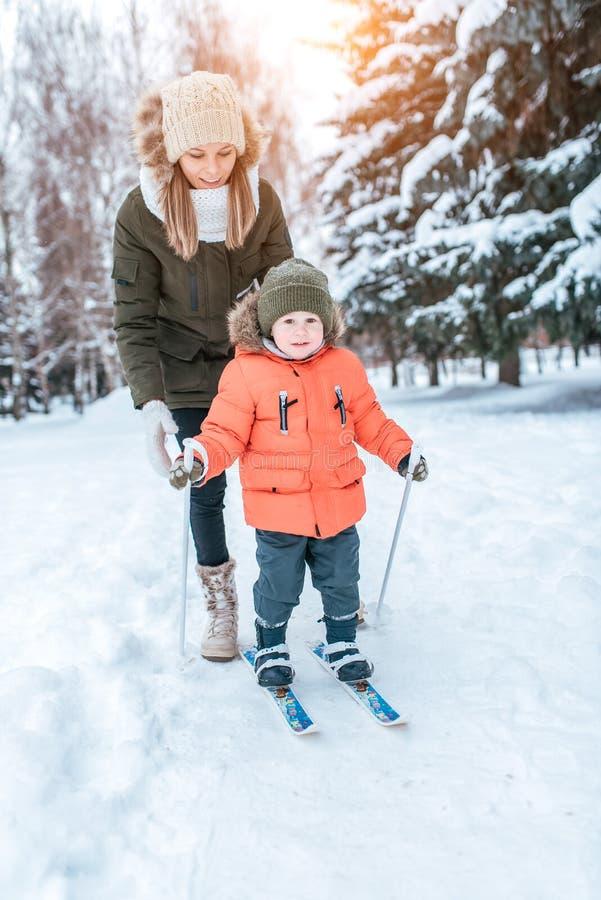 De jonge moeder verzekert de skis van de kinderen van het steunenkind, weinig jongenszoon van 3 jaar De winter bospark, achtergro royalty-vrije stock foto
