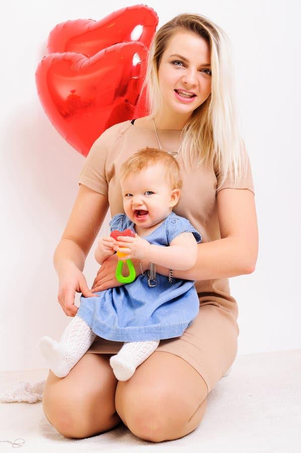De jonge moeder zit met weinig dochter op handen stock foto's