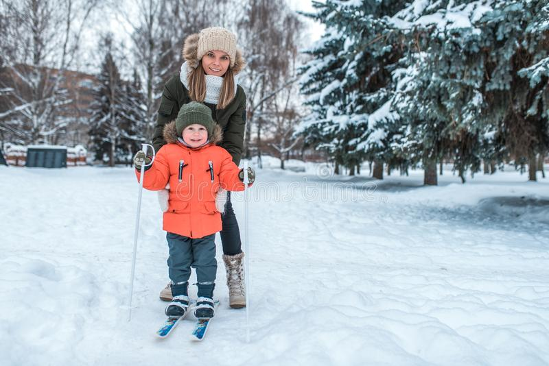 De jonge moedervrouw houdt een kleine jongen oud 2-3 jaar, zoon in de winterkleren In de winter in het hout in de toevlucht royalty-vrije stock afbeelding