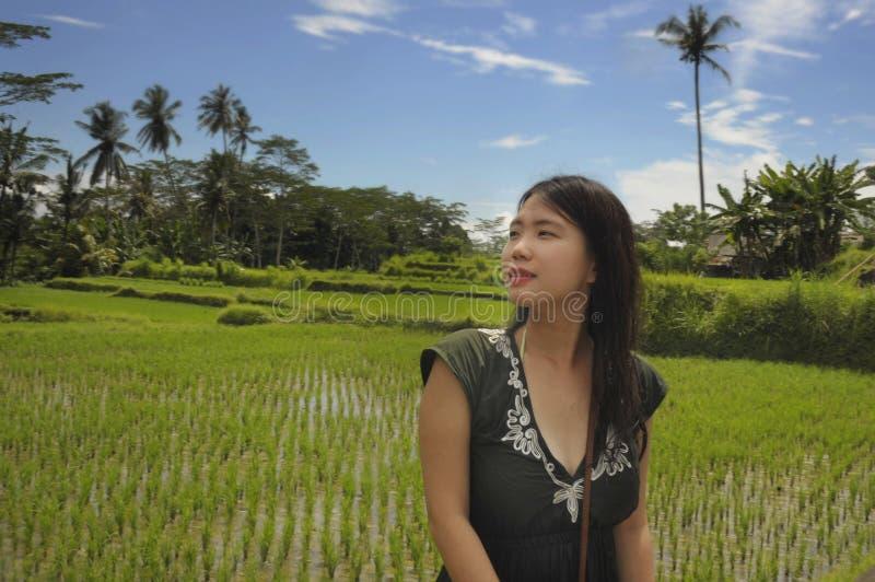 De jonge mooie Aziatische Chinese toerist die wildernis en padieveldstootkussengebied in Bali Indonesië onderzoeken ontspande en  stock afbeelding