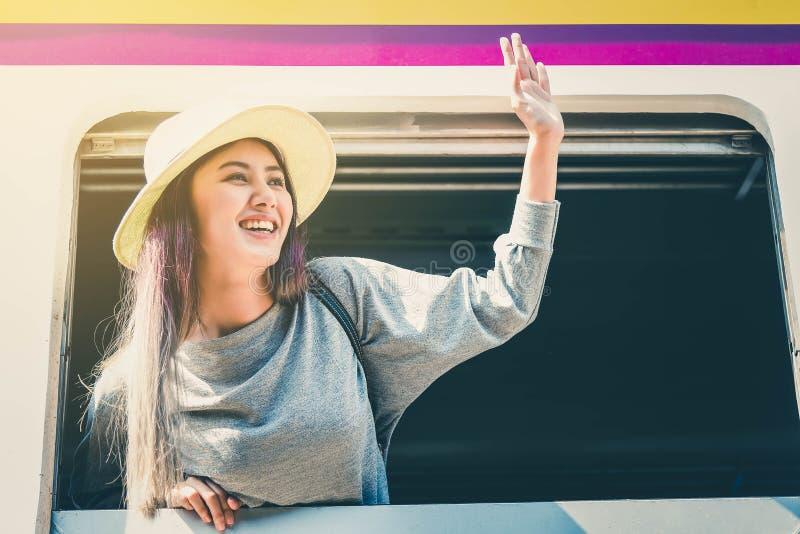De jonge mooie Aziatische hand van vrouwengolven aan vriend op trein stock foto's
