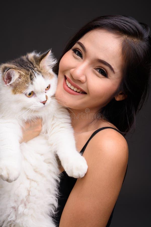 De jonge mooie Aziatische Perzische kat van de vrouwenholding stock fotografie