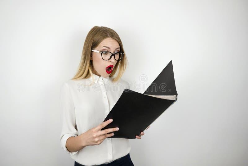 De jonge mooie bedrijfsvrouw die in oogglazen verrast zwarte omslag met documenten bekijkt isoleerde witte achtergrond royalty-vrije stock foto