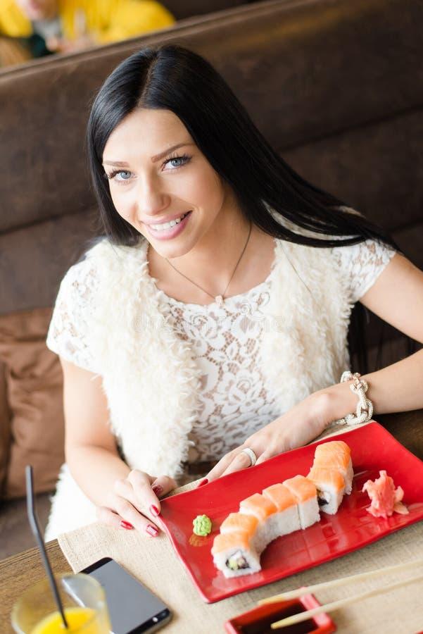De jonge mooie blauwe ogen sexy vrouwelijke zitting in een restaurant of de koffie winkelt met een plaat van sushi en mobiele tel stock afbeeldingen