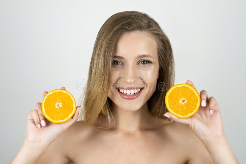 De jonge mooie blonde sinaasappelen van de vrouwenholding in haar handen die gelukkige geïsoleerde witte achtergrond kijken royalty-vrije stock afbeeldingen