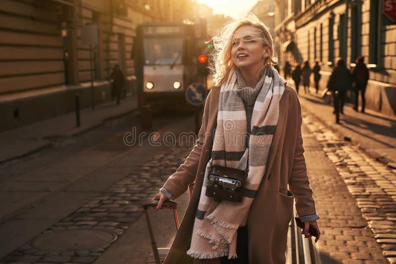 De jonge mooie blonde vrouwentoerist met een reiszak op wielen en een uitstekende filmcamera komt aan een nieuwe stad op zonnig a royalty-vrije stock fotografie
