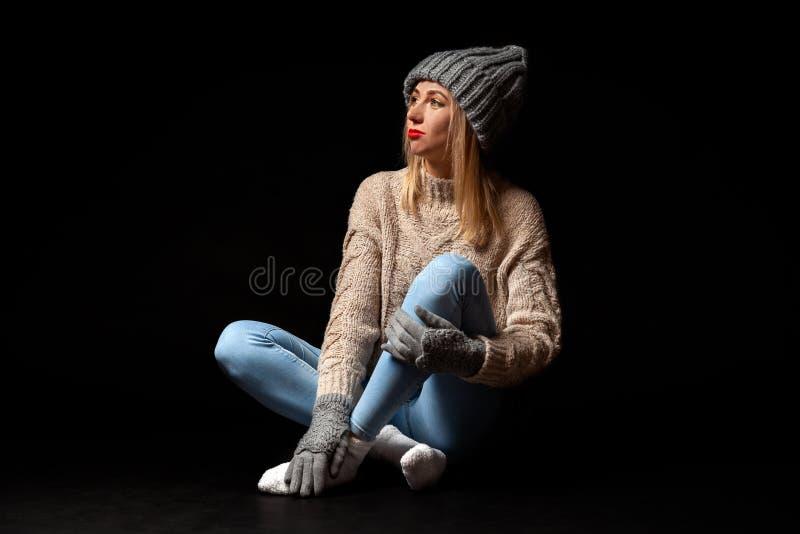 De jonge mooie blondevrouw in gebreide handschoenen en de hoed in grijs, jeans, beige sweater zitten op de vloer met gekruiste be royalty-vrije stock fotografie
