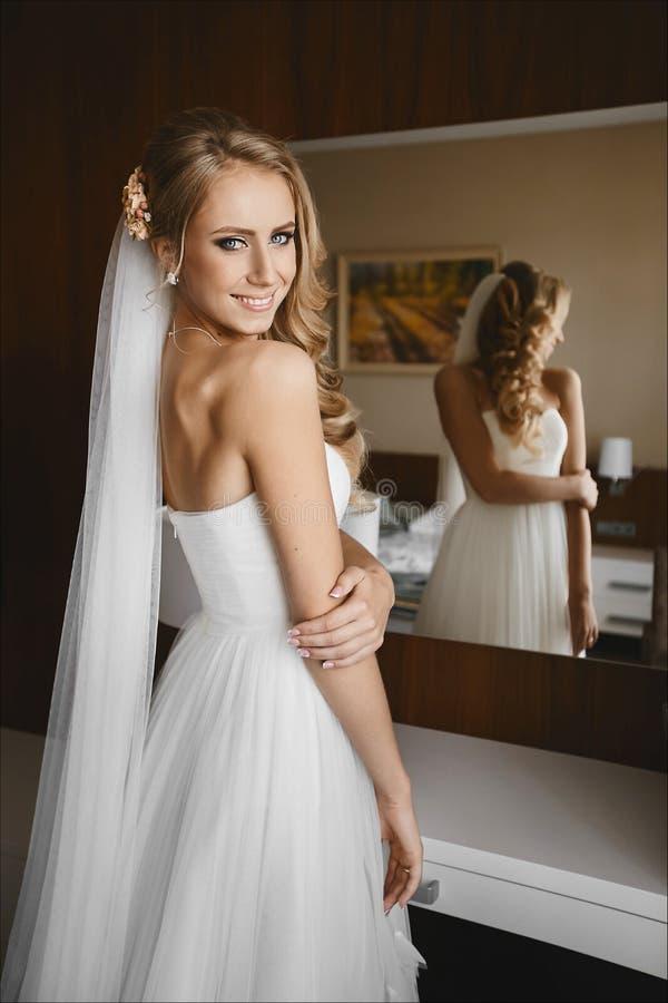 De jonge mooie bruid met blauw ogen en blondehaar bevindt zich voor de spiegel royalty-vrije stock afbeelding