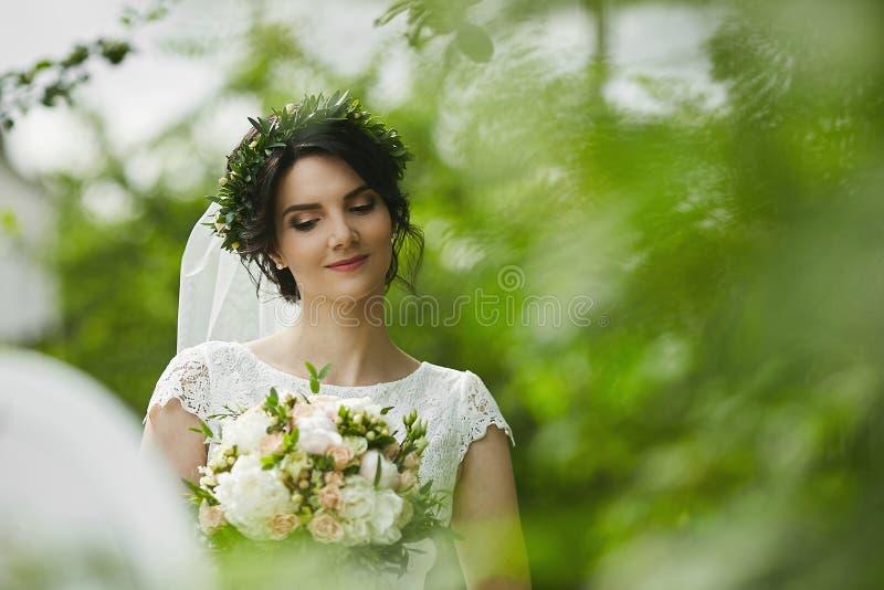 De jonge mooie bruid met groene bloemenkroon in haar huwelijkskapsel geniet in openlucht binnen van een boeket van roze bloemen royalty-vrije stock foto's