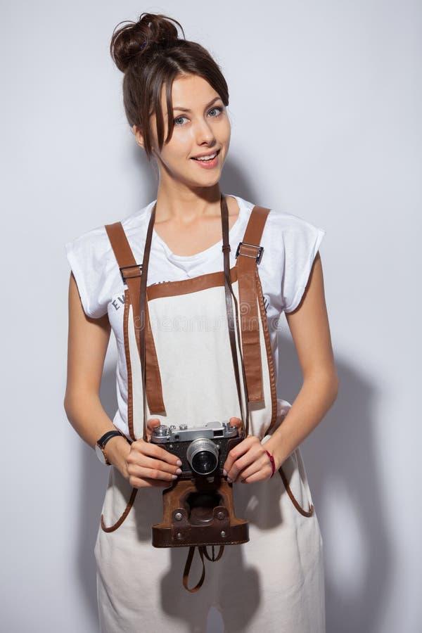 De jonge mooie camera van de vrouwenholding over witte achtergrond het bekijken camera royalty-vrije stock foto