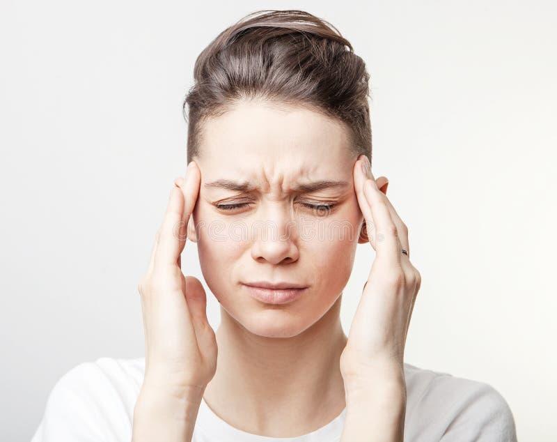 De jonge mooie die vrouw heeft hoofdpijn, op grijze achtergrond wordt ge?soleerd stock afbeelding