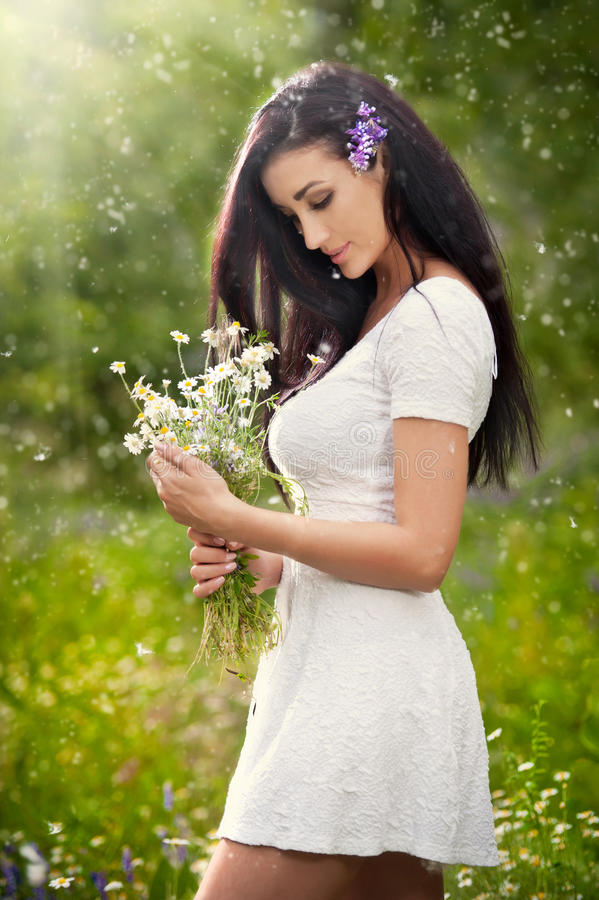 De jonge mooie donkerbruine vrouw die een wildernis houden bloeit boeket in een zonnige dag Portret van aantrekkelijk lang haarwi royalty-vrije stock fotografie