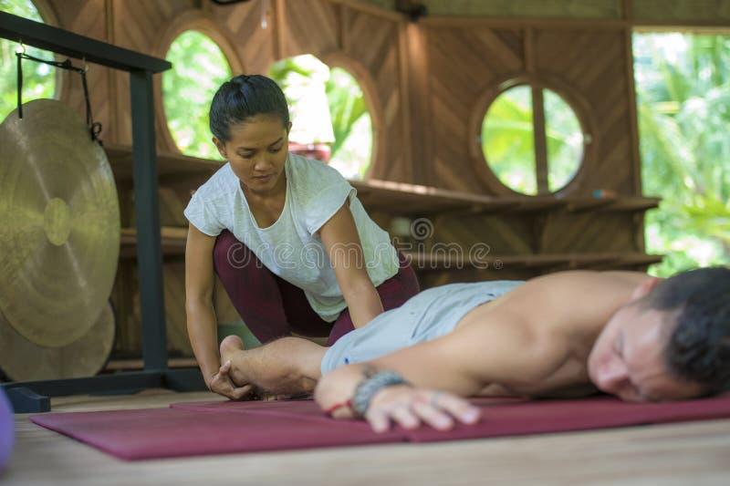 De jonge mooie en exotische Aziatische Indonesische therapeutvrouw die traditionele Thaise massage geeft aan de mens ontspande bi royalty-vrije stock fotografie