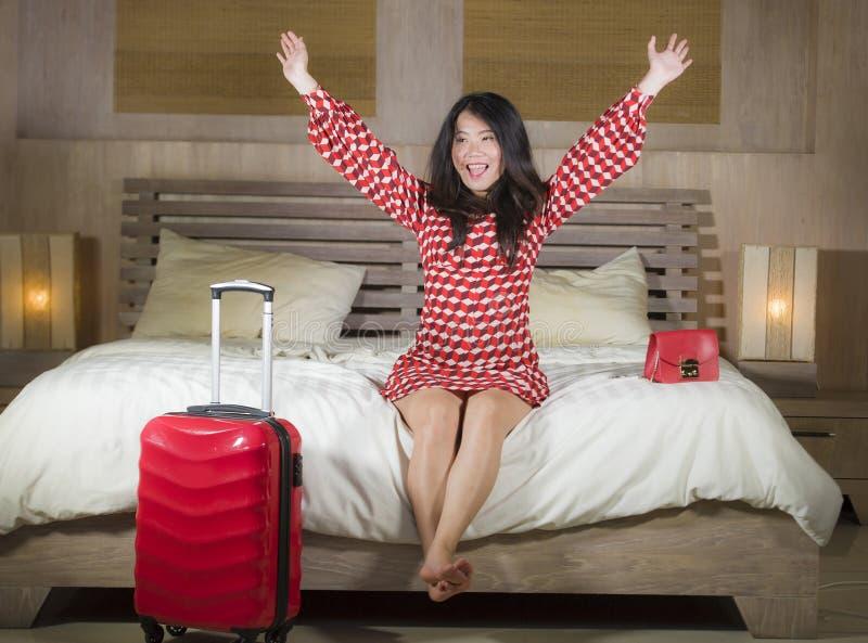 De jonge mooie en gelukkige Aziatische Chinese vrouwencontrole in de ruimte van het luxehotel ontspande en vrolijk in elegante el stock afbeelding