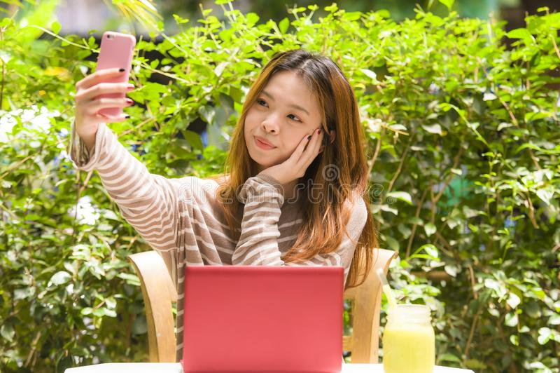 De jonge mooie en gelukkige Aziatische Chinese zitting van het studentenmeisje bij de tuin die van de koffiewinkel met laptop com stock fotografie