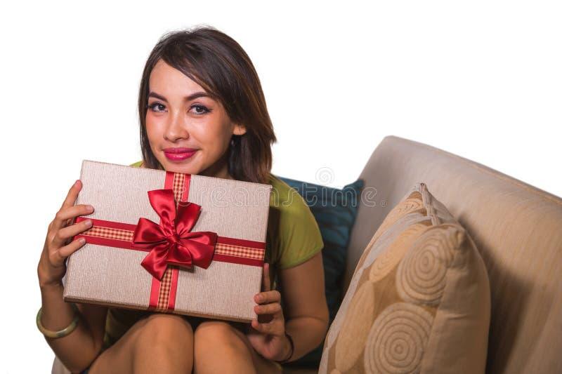 De jonge mooie en gelukkige Aziatische Indonesische aanwezige verjaardag of Kerstmis van de vrouwenholding openend de vrolijk en  stock foto's