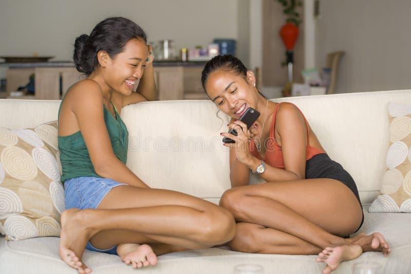 De jonge mooie en gelukkige Aziatische meisjes koppelen of zusters die van de sociale media die van Internet genieten pret samen  royalty-vrije stock afbeeldingen