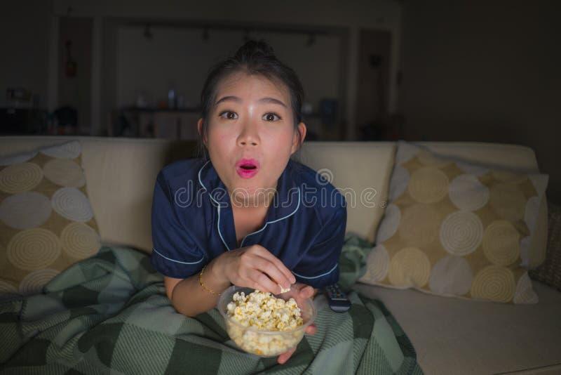 De jonge mooie gelukkige en ontspannen Aziatische Chinese van de vrouwenzitting thuis woonkamer comfortabel op banklaag die op TV royalty-vrije stock foto
