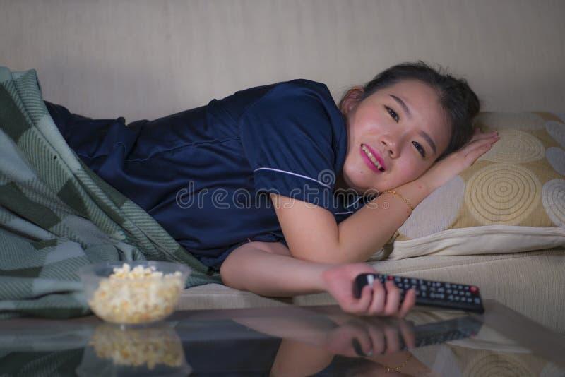 De jonge mooie gelukkige en ontspannen Aziatische Chinese vrouwen thuis woonkamer die comfortabel op banklaag die op TV letten to stock foto's