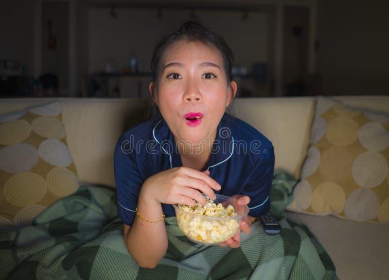 De jonge mooie gelukkige en ontspannen Aziatische Japanse van de vrouwenzitting thuis woonkamer comfortabel op banklaag die op TV royalty-vrije stock fotografie