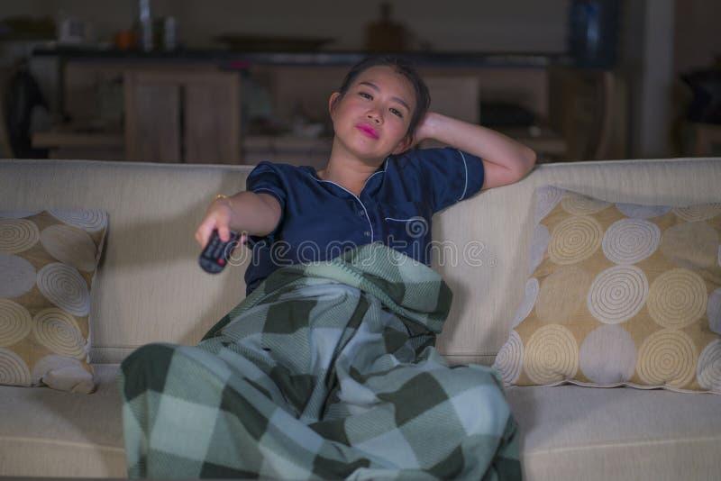 De jonge mooie gelukkige en ontspannen Aziatische Japanse van de vrouwenzitting thuis woonkamer comfortabel op banklaag die op TV stock afbeelding