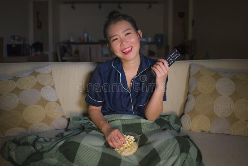 De jonge mooie gelukkige en ontspannen Aziatische Japanse van de vrouwenzitting thuis woonkamer comfortabel op banklaag die op TV stock fotografie
