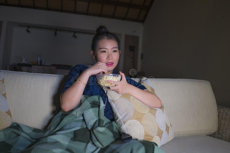 De jonge mooie gelukkige en ontspannen Aziatische Koreaanse van de vrouwenzitting thuis woonkamer comfortabel op banklaag die op  royalty-vrije stock fotografie