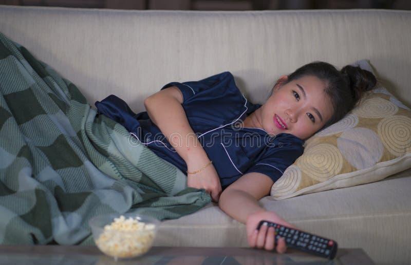 De jonge mooie gelukkige en ontspannen Aziatische Koreaanse vrouwen thuis woonkamer die comfortabel op banklaag die op TV letten  royalty-vrije stock afbeelding