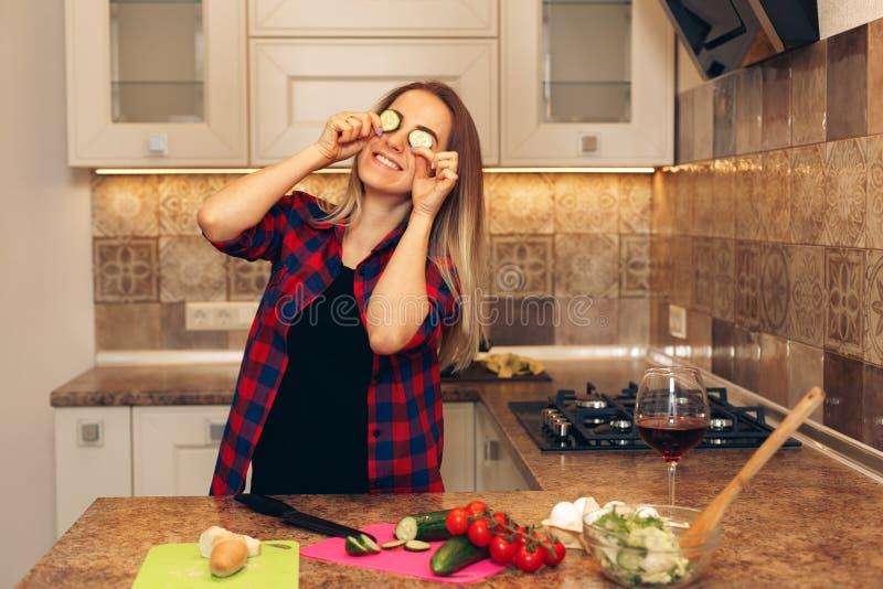 De jonge, mooie, gelukkige vrouw houdt één of andere komkommer stock fotografie