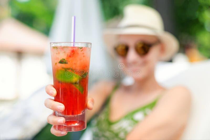 De jonge mooie gelukkige vrouwenholding ter beschikking en geeft glas met de verse koude cocktail van aardbei niet-alkoholische m royalty-vrije stock foto