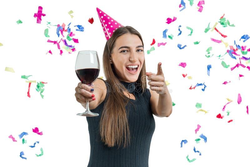 De jonge mooie glimlachende donkerbruine vrouw met glas van rode wijn en het dragen van partijhoed richt haar vinger op u, op wit royalty-vrije stock foto